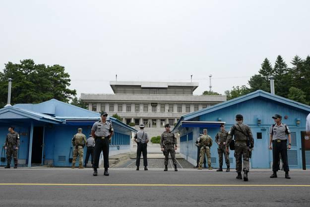 """Das """"Waffenstillstandsdorf"""" Panmunjom an der Grenze der beiden Koreas: Die Waffenstillstandslinie führt genau durch die Mitte der blauen Verhandlungsbaracken."""