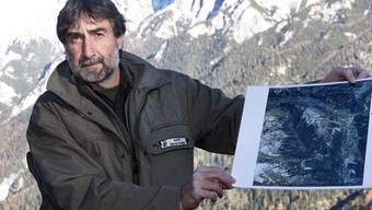 Der Wildbiologe Hannes Jenny zeigt eine Luftaufnahme des Wolfsgebietes
