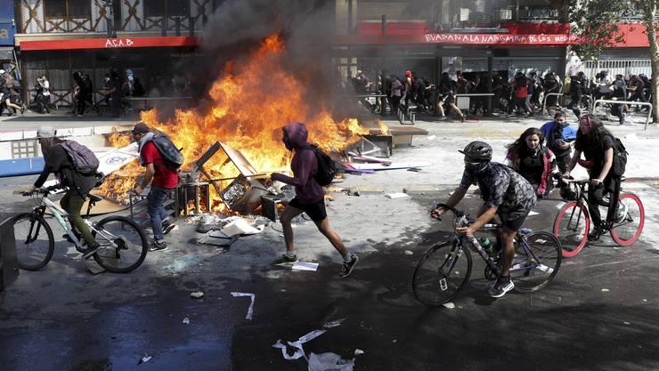 Demonstranten liefern sich in Santiago de Chile heftige Strassenschlachten mit den Sicherheitskräften. Bild: Miguel Arenas/AP