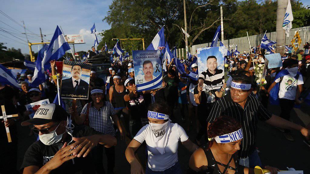 Demonstrierende in Managua mit Fotos von Personen, die bei früheren Kundgebungen in Zusammenstössen mit der Polizei getötet wurden.