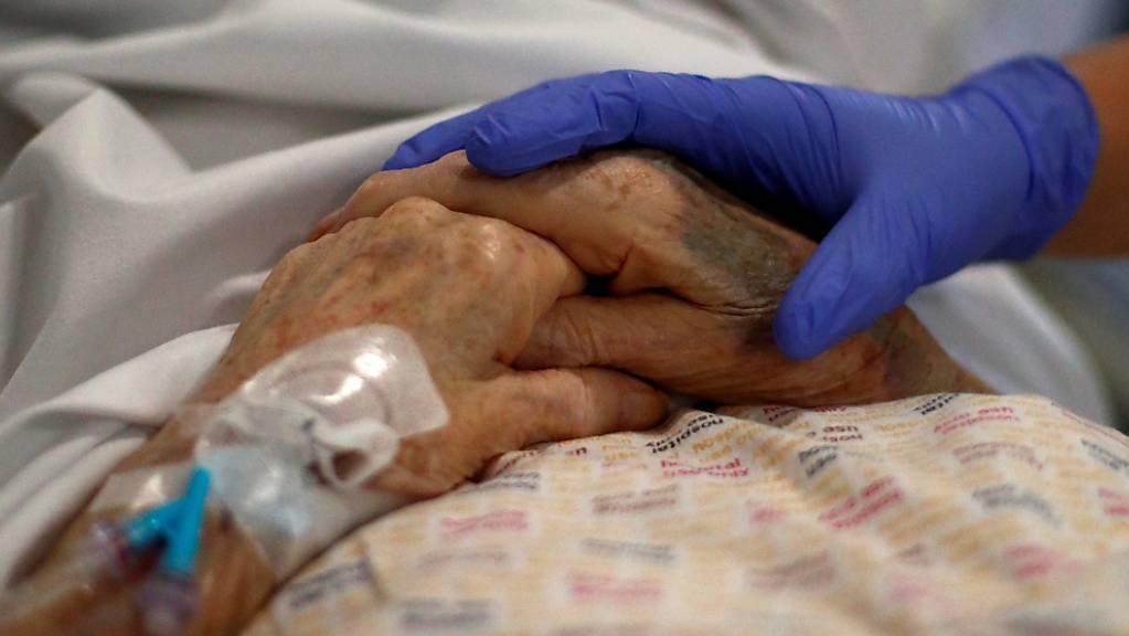 Ein Radiologe hält die Hand eines Patienten im Royal Blackburn Lehrkrankenhaus, bevor er geröntgt wird.