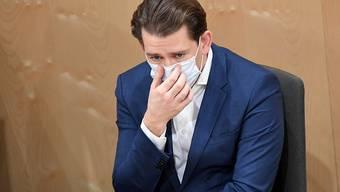 Sebastian Kurz (ÖVP), Bundeskanzler von Österreich, richtet sich während einer Sondersitzung des Nationalrates im Parlamentsausweichquartier in der Wiener Hofburg seinen Mund-Nasen-Schutz. Foto: Roland Schlager/APA/dpa