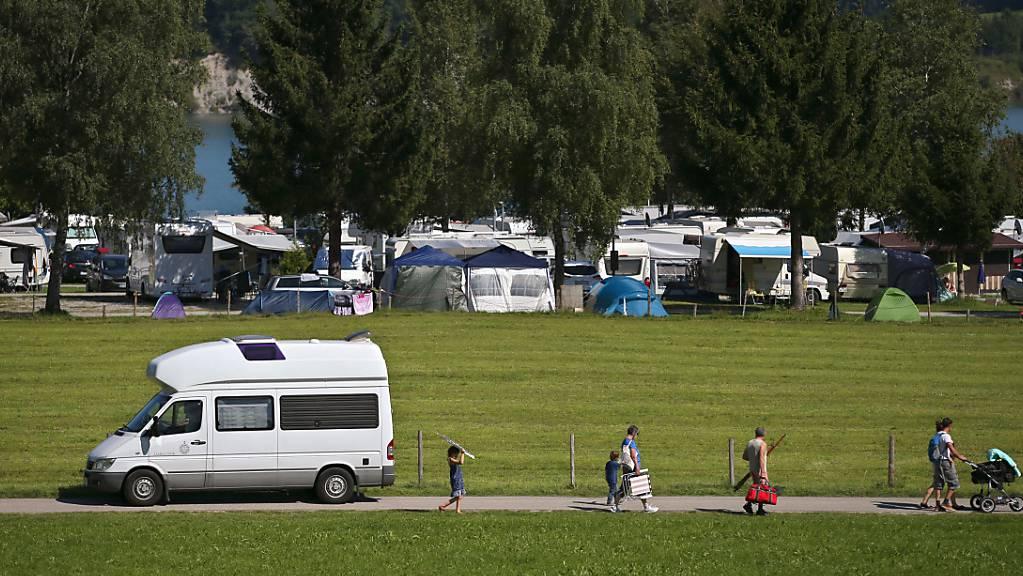 Wohnwagen und Wohnmobile stehen auf einem Campingplatz am Forggensee bei Dietringen (Bayern).