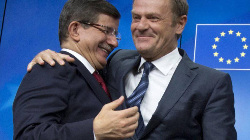 Der türkische Ministerpräsident Ahmet Davutoglu (links) in freundschaflicher Umarmung mit EU-Ratspräsident Donald Tusk. Davutoglu ist sichtlich zufrieden nach dem Gipfeltreffen EU-Türkei am Sonntag in Brüssel.