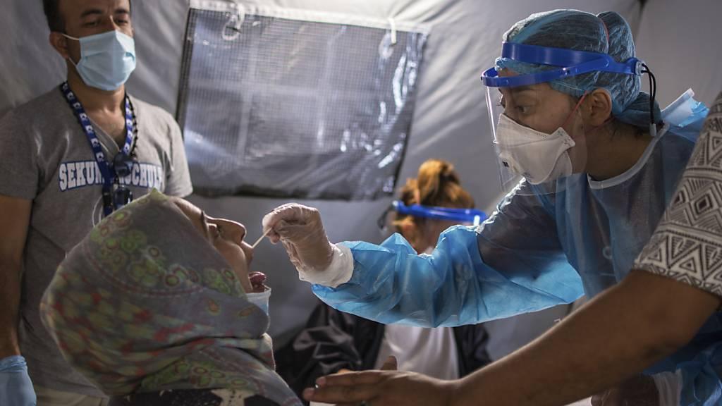 ARCHIV - Im Flüchtlingslager Moria wird einer Frau ein Abstrich aus dem Mund entnommen, um einen Corona-Test durchzuführen. Foto: Panagiotis Balaskas/AP/dpa