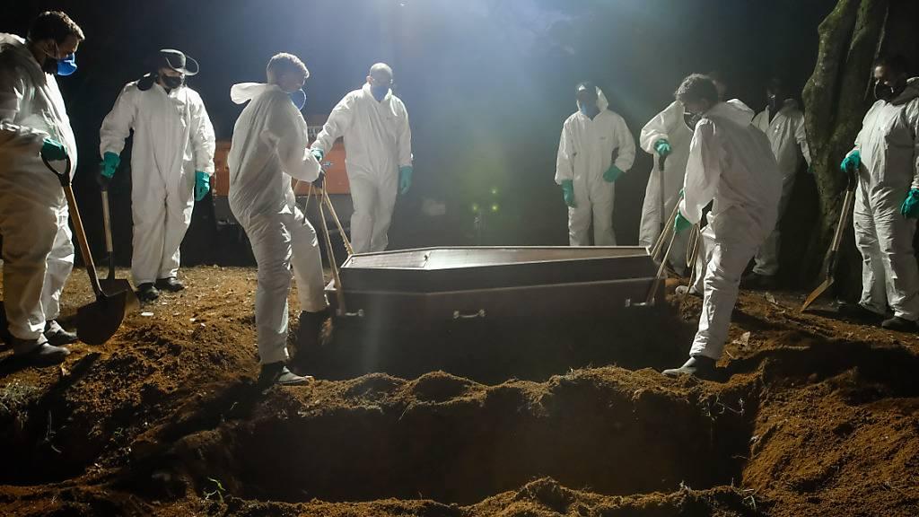 ARCHIV - Mitarbeiter des Friedhofs Vila Formosa, dem größten in Lateinamerika, tragen einen Sarg, um eine an Covid-19 verstorbene Person zu beerdigen. Aufgrund der hohen Sterbefälle, arbeiten die Mitarbeiter auch während der Nacht. Foto: Lincon Zarbietti/dpa