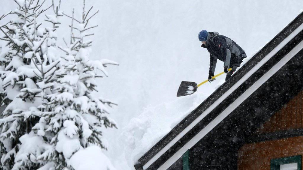 Ein Mann befreit ein Dach von der Schneelast am Mittwoch in der Nähe von Untertauern in Österreich.