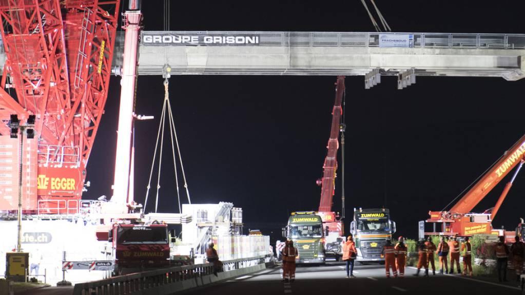 Ein riesiger Kran stand in der Nacht auf Dienstag im Waadtland im Einsatz. In Bursins ersetzten 60 Bauarbeiter eine alte Autobahnbrücke über die A1 zwischen Lausanne und Genf.