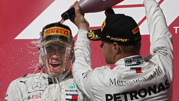 Eine verdiente Dusche für den neuen und alten Weltmeister (links) von Teamkollege Valtteri Bottas