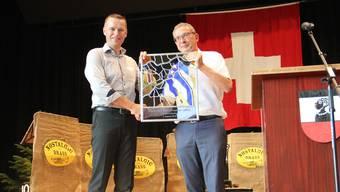 Gemeindeammann Lukas Erne (links) darf an der Festeröffnung in der Turnhalle eine Wappenscheibe von Landstatthalter Urs Hofmann entgegennehmen. CM