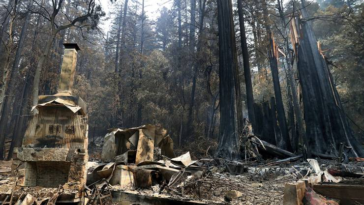 """Die Feuerstelle des """"Nature Lodge Museum and Store"""" im """"Big Basin Redwoods State Park"""" steht umgeben von Verwüstungen durch die verheerenden Waldbrände. Foto: Shmuel Thler/The Santa Cruz Sentinel/AP/dpa"""