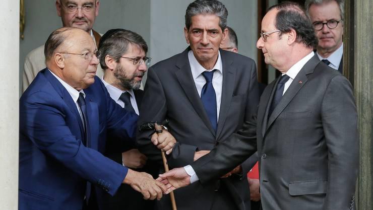 Präsident Hollande (rechts) schüttelt dem Rektor der Grossen Moschee von Paris, Boubakeur (links), die Hand.