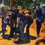Sicherheitskräfte helfen einem Verletzten, der vor den Geiselnehmern in einem Restaurant in Bangladesch fliehen konnte.