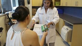 Eine Schwangere in Miami erhält Informationsmaterial über Zika: Der Gouverneur des Bundesstaates Florida kündigte an, dass jeder Schwangeren eine Untersuchung und ein Test für eine allfällige Zika-Infektion angeboten werden soll. (Archivbild)