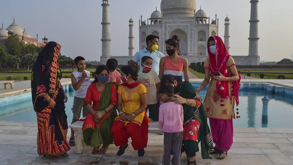 Eine Gruppe von Touristen sitzen auf einer Bank am Wasserbecken vor dem Mausoleum Taj Mahal. Aufgrund des Rückgangs von Corona-Neuinfektionen öffnet die Regierung in Indien mehrere Denkmäler. Foto: Uncredited/AP/dpa
