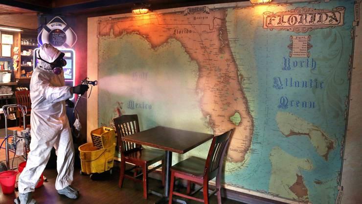 Ein Arbeiter im Schutzanzug desinfiziert die Florida-Landkarte in einem Restaurant: In den USA sind jetzt auch Staaten betroffen, die zuvor verschont blieben.