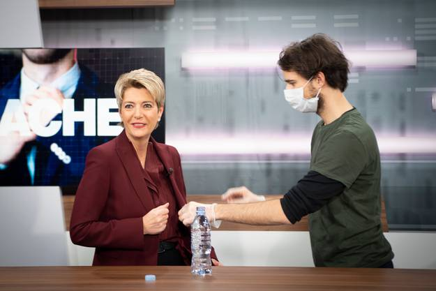 Schutz vor einer möglichen Übertragung steht auch im TVO-Studio an erster Stelle. Ein Mitarbeiter mit Handschuhen und Hygienemaske befestigt ein Funkmikrofon am Revers der Justizministerin.