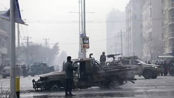 Sicherheitleute am Ort des mutmaßlichen Bombenanschlags. Foto: Rahmat Gul/AP/dpa