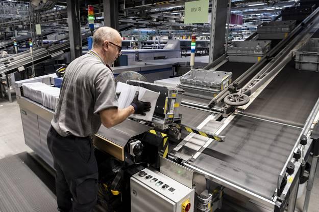 Die Mitarbeiter sind häufig nur noch Assistenten der Maschinen, wie dieser Mann, der stapelweise Briefe in die Sortiermaschine lädt.