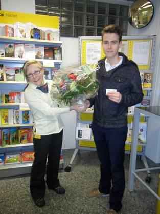 Andrea Jaussi überreicht Alain Kaiser die Kreditkarte und einen Blumenstrauss