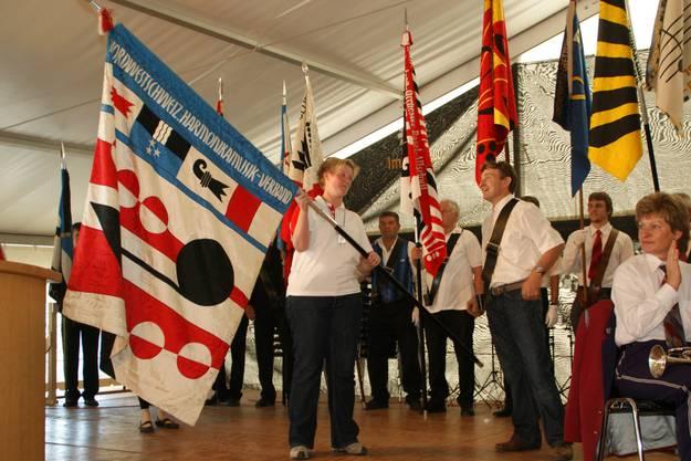 OK-Präsidentin Pia Siegenthaler übernimmt die Fahne der Region Nordwestschweiz, die nun für vier Jahre in Staffelbach bleiben wird