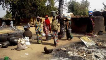 Frauen verlassen mit ihren Habseligkeiten ein von Boko Haram angegriffenes Dorf. (Archiv)