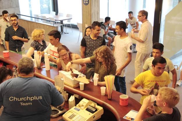 Jugendarbeiter Matthias Arn (vorne links) verteilt im Cafe der reformierten Kirchgemeinde nach dem gemeinsamen Abendessen Eis an alle Flüchtlinge und Einwohner.