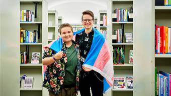 Jean (l.) mit Anouk Neracher, die das Projekt «Trans* Living Library» in der Stadtbibliothek Aarau aufgegleist hat. Auf der Trans-Pride-Flagge steht Blau für männlich, Rosa für weiblich und Weiss für non-binär.Bild: C. Frei