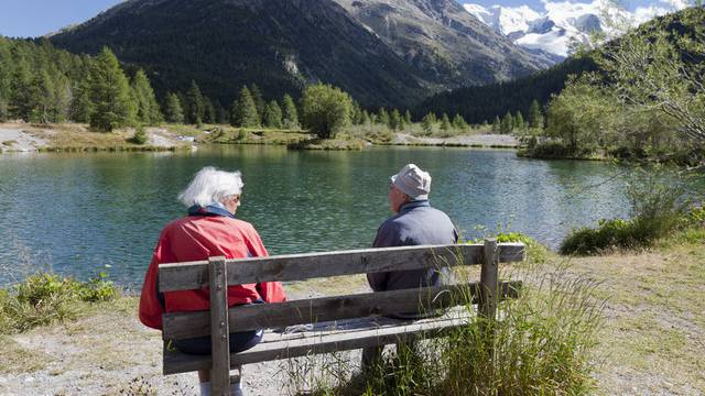 Ein Rentnerpaar sitzt auf einer Bank an einem See (Symbolbild)