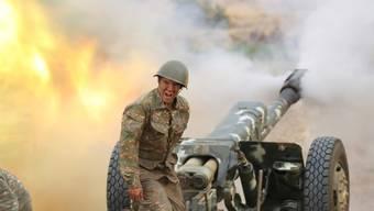 HANDOUT - Das Foto, das vom armenischen Verteidigungsministerium zur Verfügung gestellt wurde, zeigt einen Soldaten der armenischen Armee beim Abfeuern einer Kanone. Foto: -/Armenian Defense Ministry/AP/dpa - ACHTUNG: Nur zur redaktionellen Verwendung im Zusammenhang mit der aktuellen Berichterstattung und nur mit vollständiger Nennung des vorstehenden Credits.