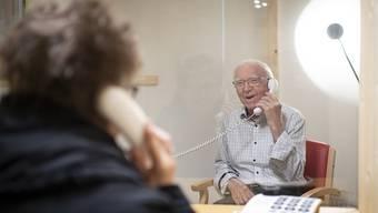 """Der 88-jährige Eugen Studach erhält Besuch von Tochter Barbara Castelberg, in der Besucherbox des Altersheims Risi in Wattwil SG. Dank der """"Bsuechsbox"""" können sich Angehörige und Bewohner trotz der Coronavirus-Pandemie treffen und über das Telefon miteinander plaudern."""