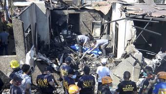 Rettungskräfte durchsuchen die Trümmer am Unglücksort.