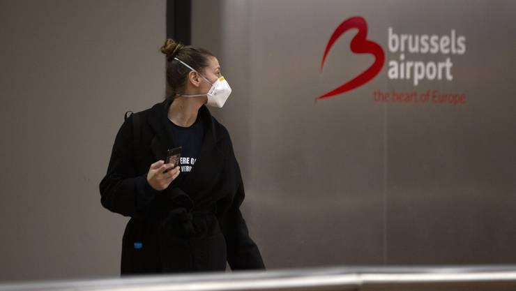 Frau mit Maske: Auch am Flughafen in Brüssel schützt man sich vor dem Virus. Das öffentliche Leben steht in der belgischen Hauptstadt nahezu still.