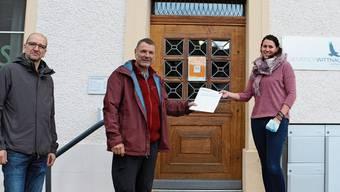 Benedikt Furrer (l.) und Samuel Freiburghaus bei der Übergabe der Initiative an Gemeindeschreiberin Claudia Schraner.