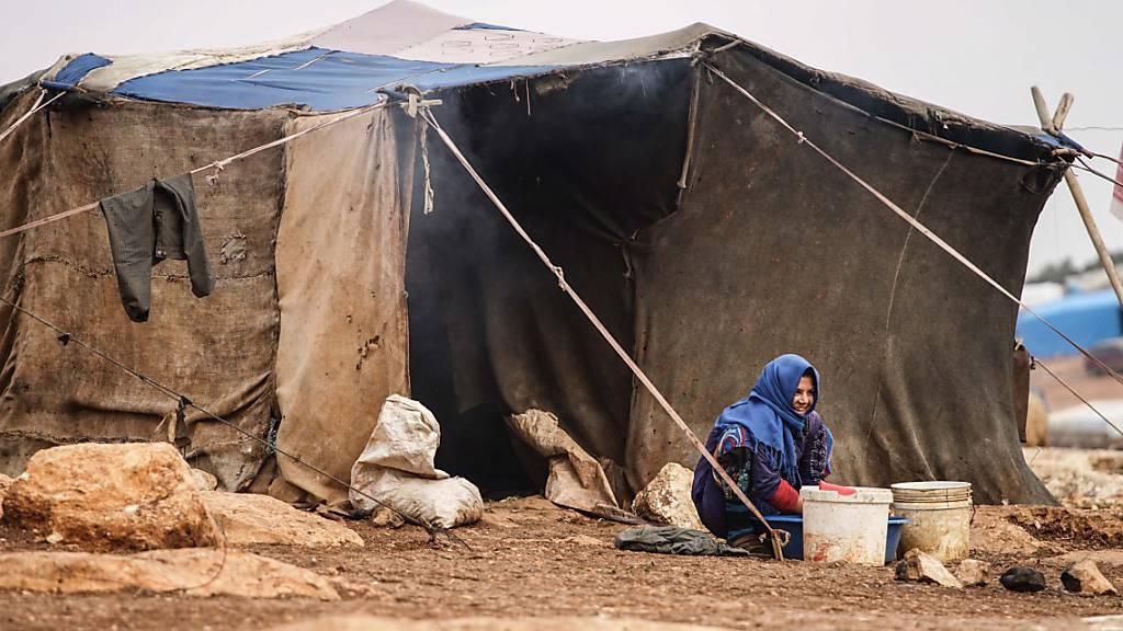 Eine in Idlib vertriebene Frau wäscht Kleider im Atamah-Camp nahe der türkischen Grenze. Nach Angaben des Uno-Nothilfebüros (Ocha) ist die Lage besonders für Frauen und Mädchen unerträglich. (Archivbild)