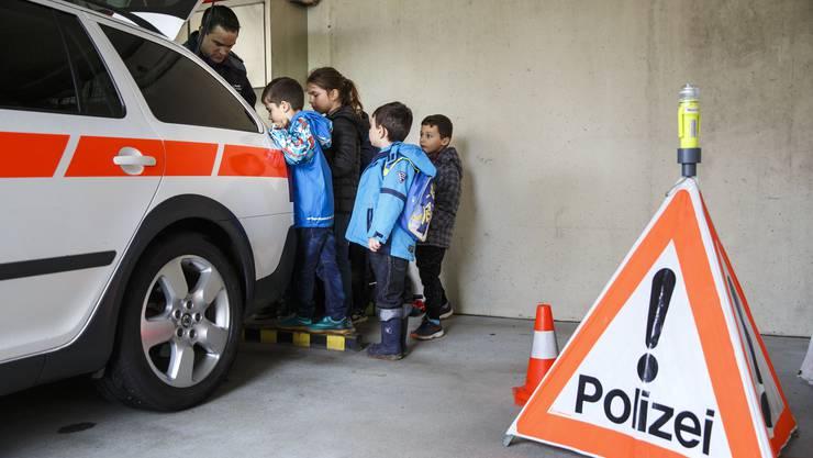 Ferienpässler aus Grenchen schauen sich ein Polizeiauto an