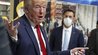 US-Präsident Donald Trump hat bei einem Besuch eine Fabrik in Michigan trotz Maskenpflicht erneut zumindest teilweise keine Schutzmaske getragen. Auf dem Bild hält er zwar eine Maske in der Hand, setzt sie aber nicht auf.