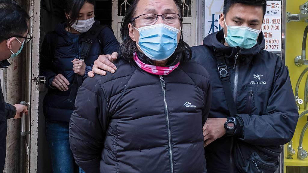 Daniel Wong Kwok-tung (l), Bezirksrat und Anwalt aus dem Stadtteil Kowloon, wird von Polizisten aus seinem Büro eskortiert. Foto: Isaac Wong/SOPA Images via ZUMA Wire/dpa