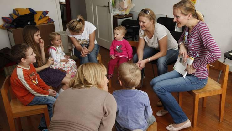 Sechs Kinder zwischen zwei und acht Jahren lauschen aufmerksam Geschichten und Märchen - auf Russisch