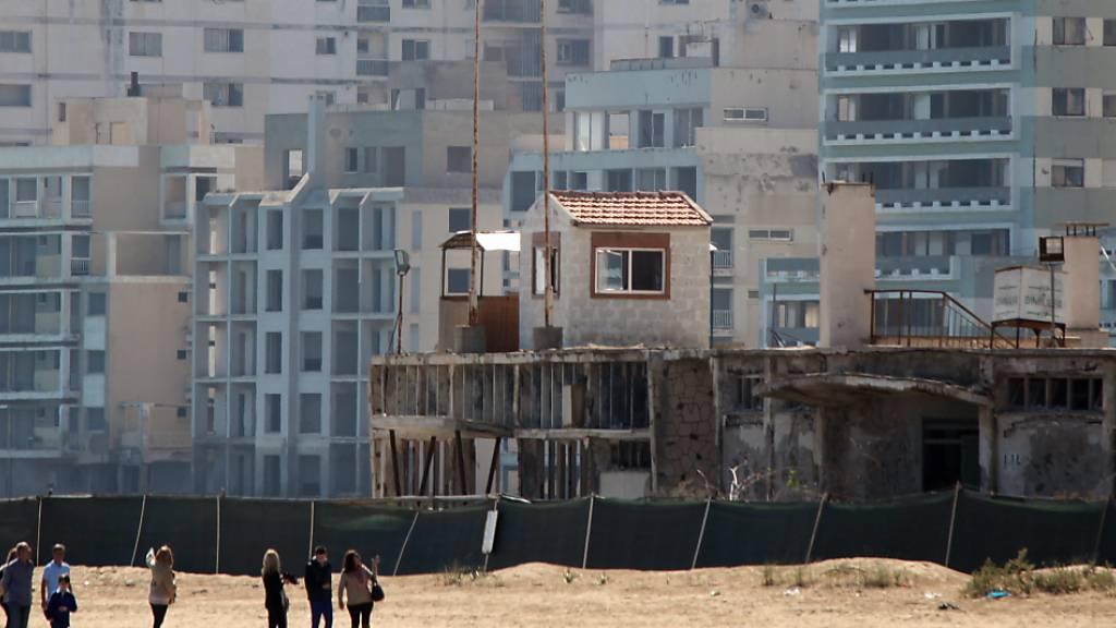 ARCHIV - Menschen spazieren am Strand bei einem militärischen Wachposten, vor verlassenen Hotels in einem vom türkischen Militär genutzten Gebiet im türkisch besetzten Gebiet in der verlassenen Küstenstadt Varosha. Foto: Katia Christodoulou/EPA/dpa