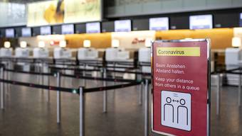 Ein Informationsschreiben verweist auf Abstand halten beim  Anstehen am Flughafen Zürich. Archivbild
