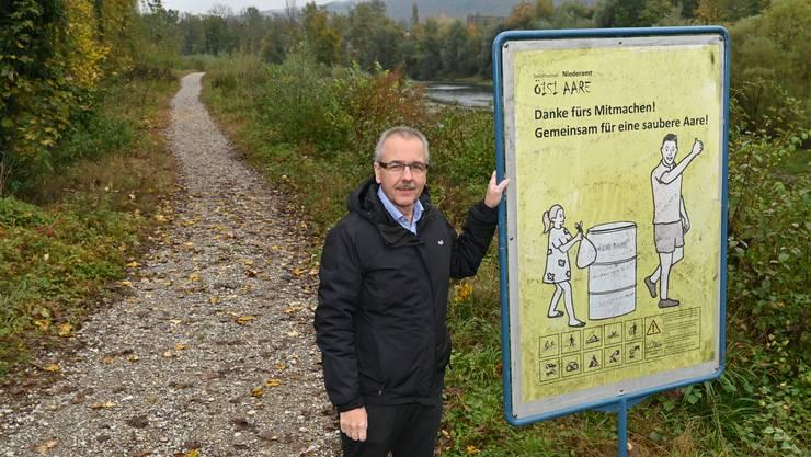 Daniel Gubler, Präsident von «Öisi Aare», zeigt ein Plakat gegen Littering am Aareufer.