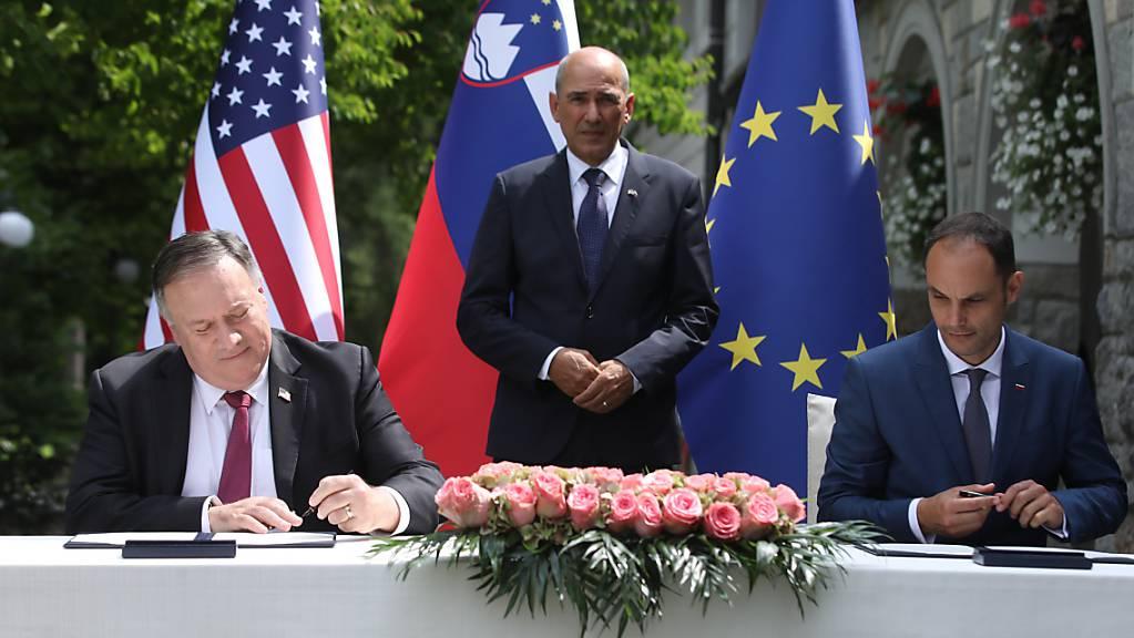 US-Aussenminister Mike Pompeo (l) und sein slowenischer Amtskollege An·e Logar (r) unterzeichnen in Anwesenheit von Ministerpräsident Janez Jansa ein Abkommen zur 5-G-Sicherheit. Foto: Anze Malovrh/STA/dpa