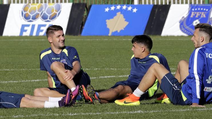 Kosovos Nati-Verteidiger Alban Pnishi (l.) entspannt sich nach dem Training mit seinen Teamkollegen.