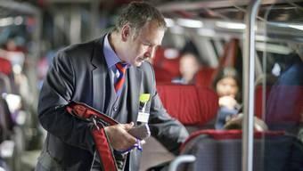 Ein Zugbegleiter kontrolliert die Tickets der Fahrgäste (Symbolbild)