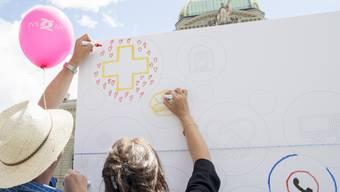 """Für die Kampagne """"Love Service public 2.0"""" des Personalverbandes des Bundes wird auf dem Bundesplatz auf einer Stellwand gezeichnet."""