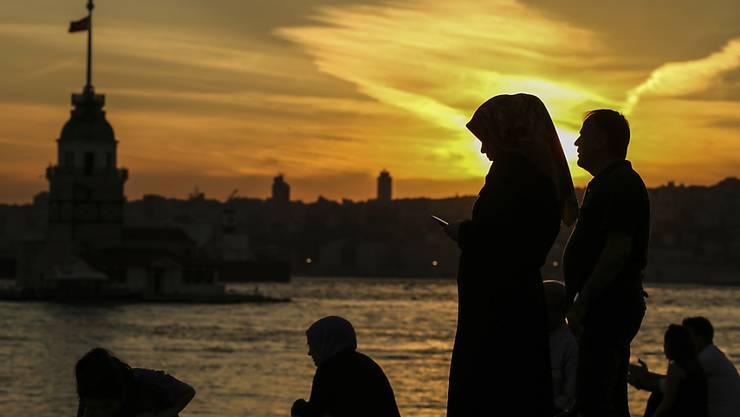 """ARCHIV - Menschen stehen im Sonnenuntergang am Bosporus. (zu dpa """"Kampf um Rollen und Regeln - Frauenmorde in der Türkei"""") Foto: Emrah Gurel/AP/dpa"""