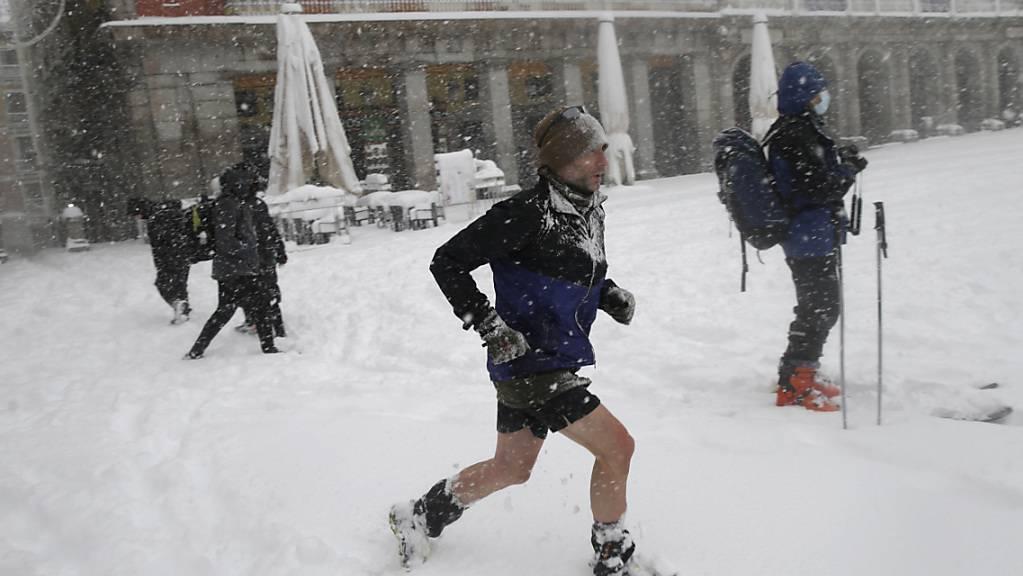 dpatopbilder - Ein Mann läuft durch den Schnee auf der Plaza Mayor. Das Sturmtief «Filomena» sorgt landesweit für Rekordkälte und viel Schnee. Laut des Wetterdienstes AEMET gab es solch einen Schneefall das letzte Mal im Februar 1984. Foto: Andrea Comas/AP/dpa