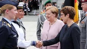 Die deutsche Kanzlerin Merkel und die neue Verteidigungsministerin Kramp-Karrenbauer begrüssen Rekrutinnen und Rekruten.