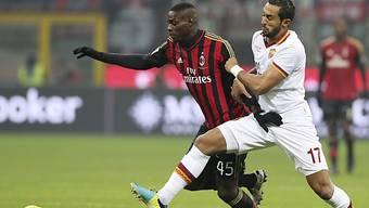 Roma-Verteidiger Benatia wehrt sich gegen Milan-Stürmer Balotelli.